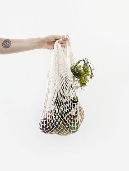 Frauenarm, der einen Netzbeutel mit unverpackten Lebensmitteln in der Hand hält