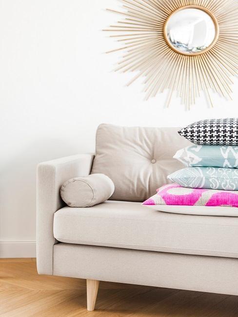 Sofa in Beige mit vielen Dekokissen, darüber ein goldener Sonnen-Spiegel zur Deko an der Wand