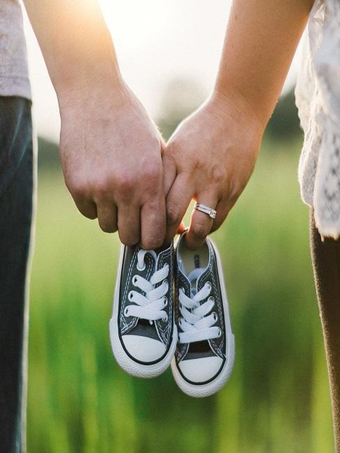 Ein Paar von hinten, Händchen haltend, mit zwei Babyschuhen in der Hand
