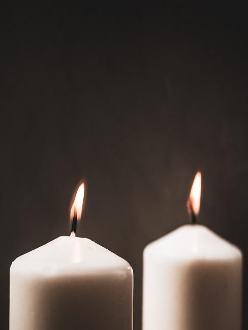 Zwei weiße brennende Kerzen stehen nebeneinander als Taufgeschenk