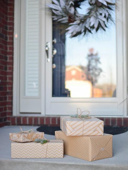 Fenster von außen, davor liegen auf dem Brett verpackte Geschenke