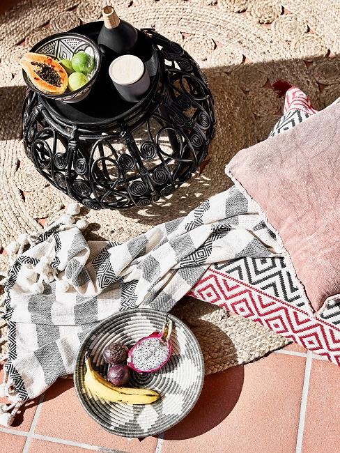 Ein runder Jute-Teppich auf einer gefliesten Terrasse, darauf ein kleiner Mettall-Beistelltisch und zwei Boho Kissen