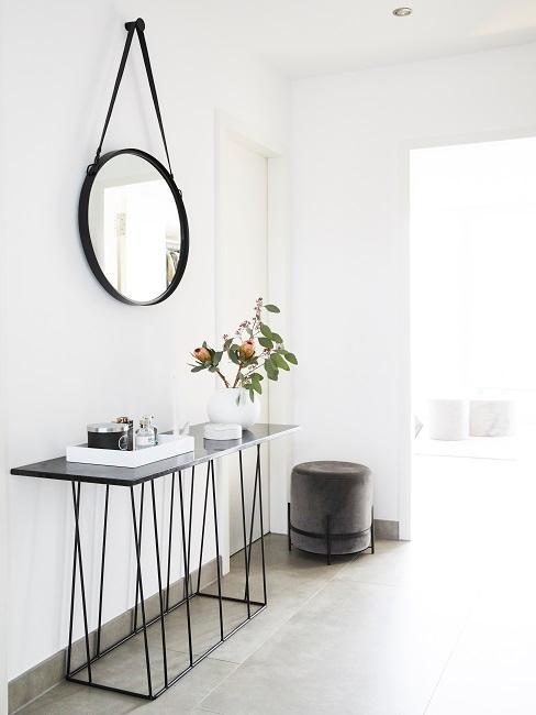 Weißer Flur mit hellem Boden, eine schwarze Konsole an der Wand mit Deko in Weiß und darüber ein schwarzer Wandspiegel