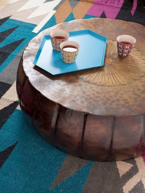 Ein bunter Teppich mit Ethno Muster kombiniert mit einem runden Holz-Couchtisch