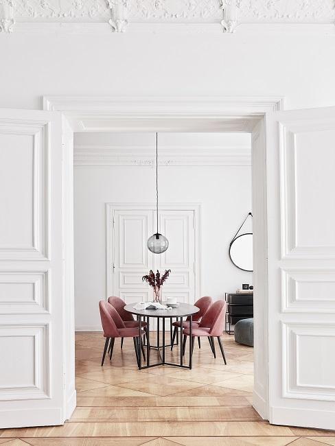 Wohnung mit luxuriösen, hohen Stuckdecken, passend dazu ein hochwertiger Holz-Esstisch mit Samt-Stühlen und eine elegante Pendelleuchte