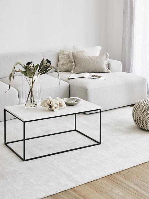 Lagom Wohntrend weißes Wohnzimmer mit Couchtisch mit Deko, Pouf, Sofa mit Kissen aus Leinen