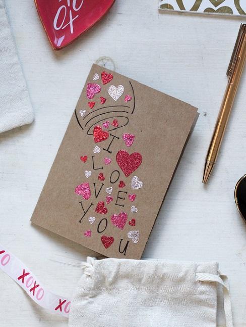 Valentinstag Sprüche Karte aus Kraftpapier mit rosa und roten Herzen