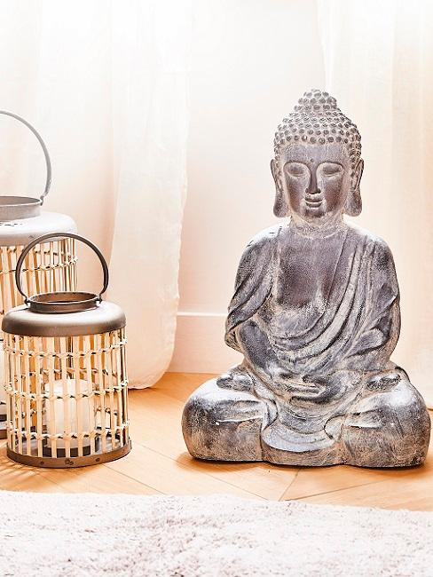 Asiatische Deko Buddha auf dem Boden neben Laternen
