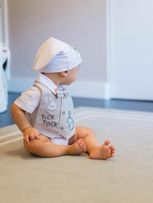 Baby Junge mit Mütze sitz auf dem Boden