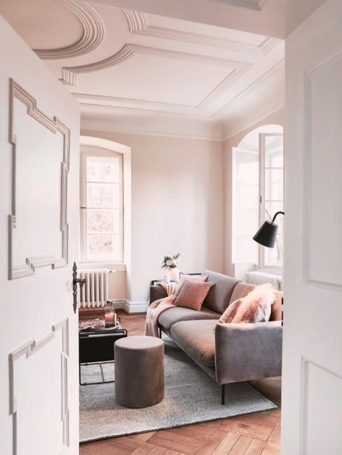 Salón con techos con molduras, sofá grisáceo con cojines y decoraciones en tonos rosados