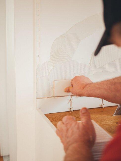 manos haciendo pequeñas obras en una pared