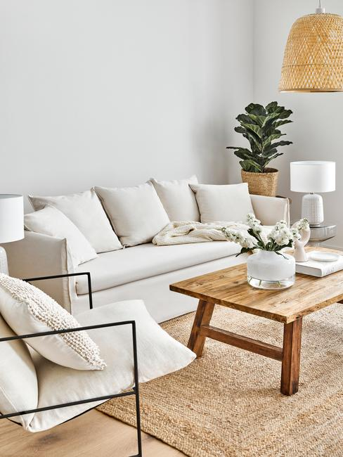 Sofá Mila en tono crema en un salón etno con mesa baja de madera, alfombra de ratán, planta y lámpara de mimbre