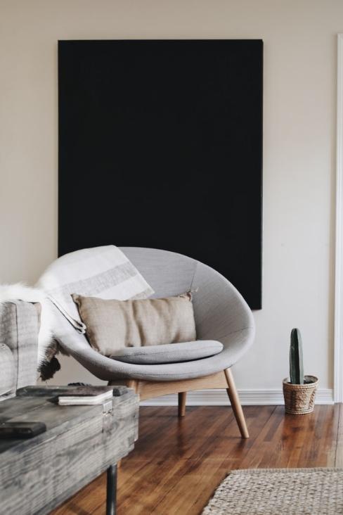 Fauteuil rond en textile gris avec pieds en bois et tableau noir