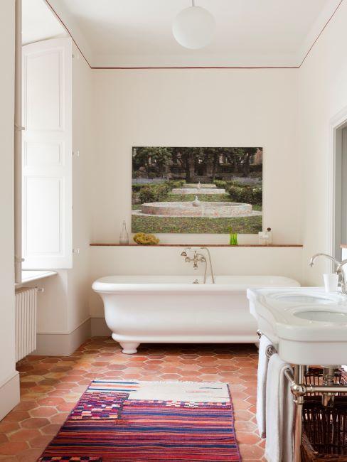 Salle de bain blanche avec carrelage terracotta et tapis ethno