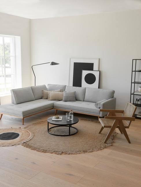 Salon moderne avec canapé gris, tapis en jute et fauteuil en cannage