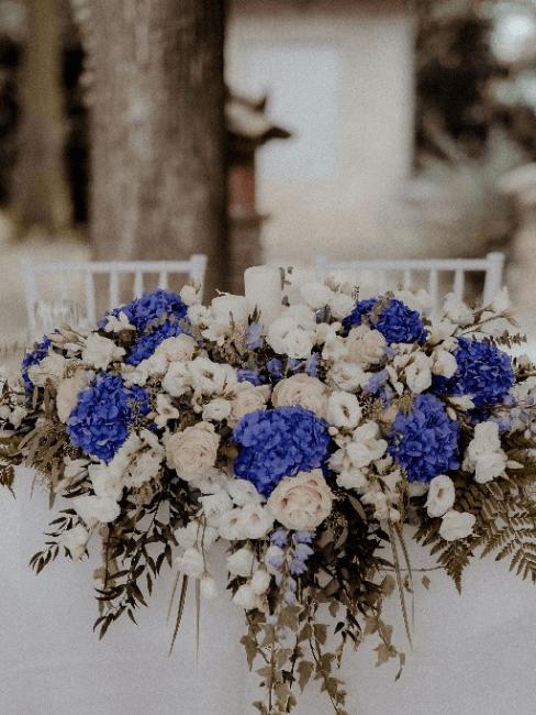 Montage de fleurs blanches roses et bleu pour table de mariage
