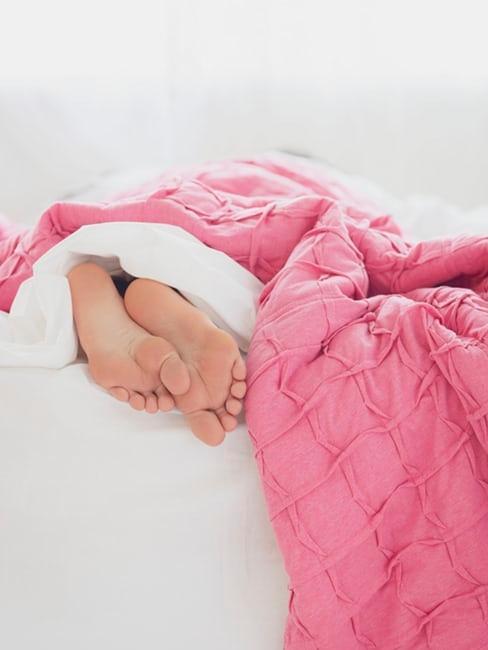 piedi sotto piumone rosa