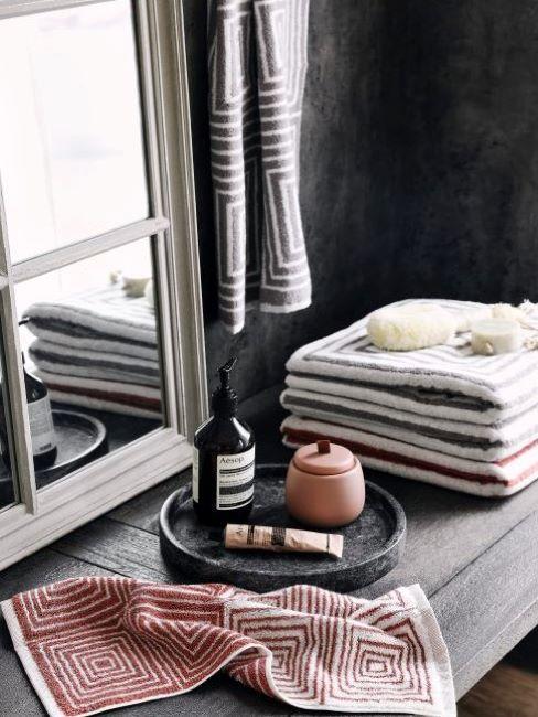 bagno nero con asciugamani in colori pastello e specchio