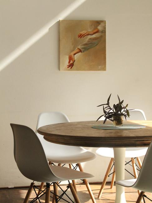 Houten eettafel met witte stoelen op de achtergrond van de muur met ingelijste print