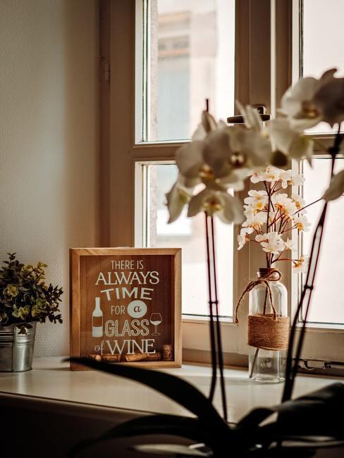 Romantische raamdecoratie met bloemen en transparante vaas