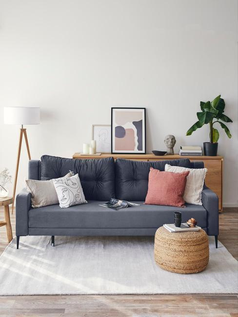 Woonkamer shabby chic met zitbank met vele sierkussens, rotan kruk, vloerlamp en plantenpot