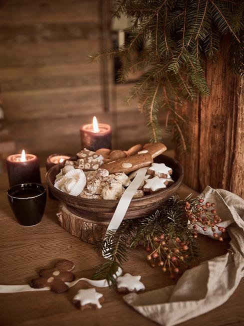 Drewniana misa z różnymi rodzajami ciastek świątecznych obok świeczek w kuchni