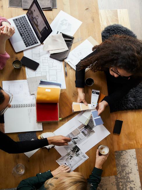 Trzy osoby siedzące przy drewnianym stole w biurze i pracujące