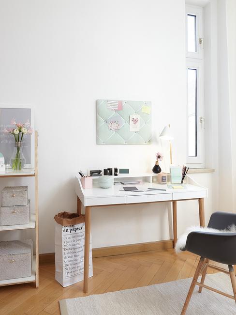 Przestrzeń domowego biura z białym biurkiem, czarnym krzesłem oraz dekoracjami w postaci regału z kwiatami
