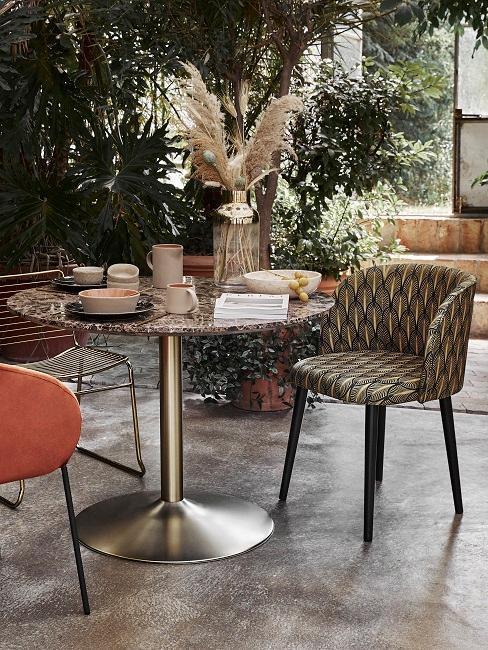 Czarny, marmurowy stół z trzema krzesłami w różnych kolorach z trawą pampasową jako dekoracją