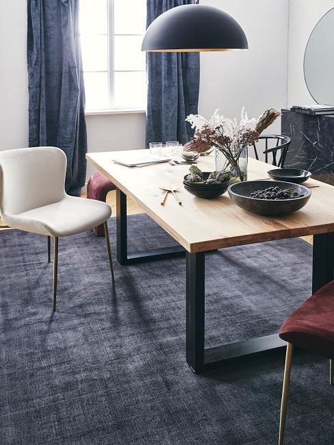 Jadalnia z białymi ścianami, niebieskim dywanem, zasłonami oraz zastawą