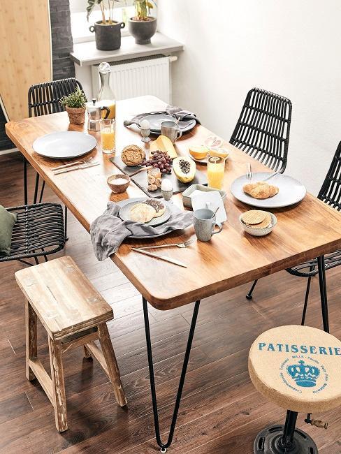 Mała jadalnia z drewnianym stołem, czarnymi krzesłami, drewnianym stołkiem oraz zastawą na stole