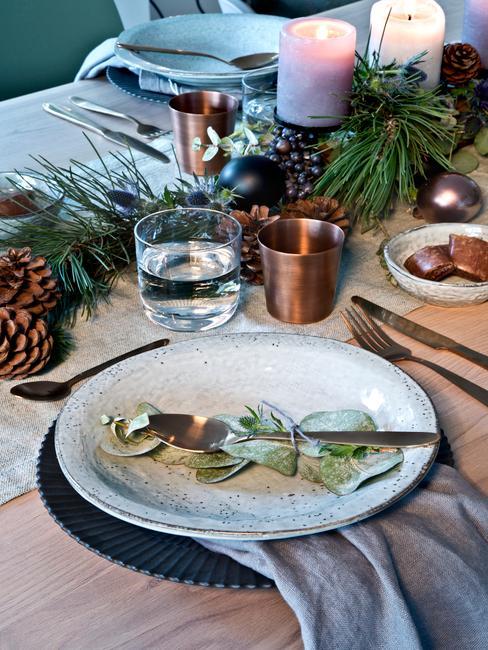 Zastawiony stół świąteczny z dekoracjami z szyszek oraz świerku