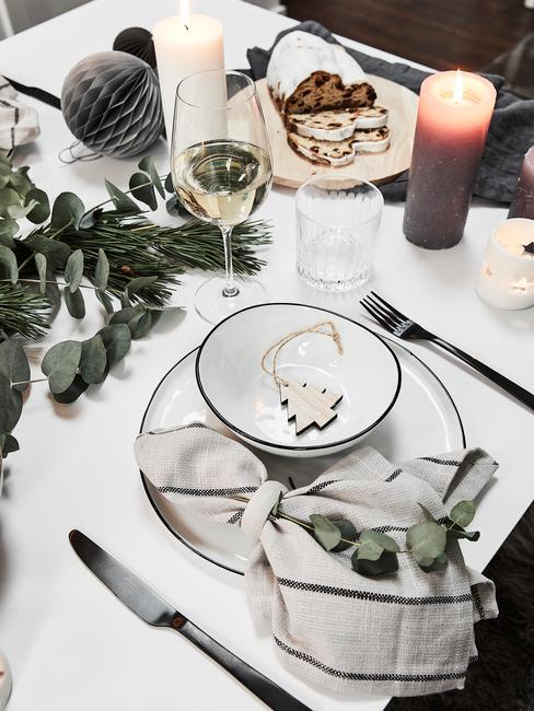 Zastawiony stół z białym obrusem, świeczkami oraz eukaliptusem oraz świąteczną dekoracją