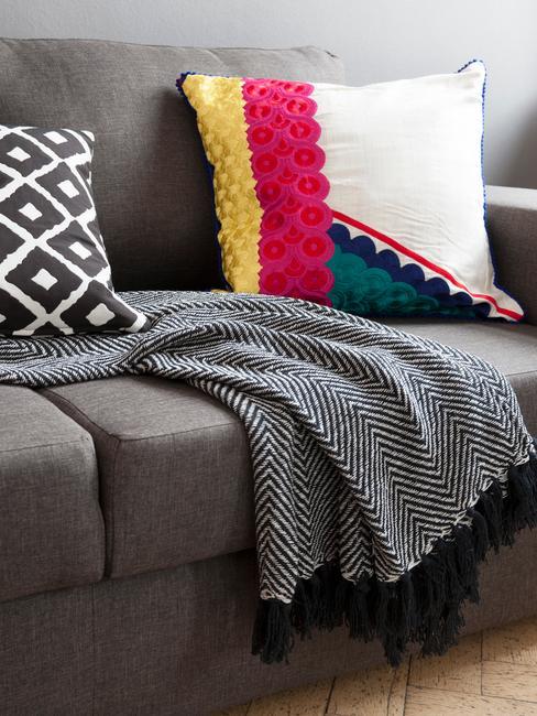 Szara sofa w salonie udekorowana poduszkami w stylu etno roaz kocem