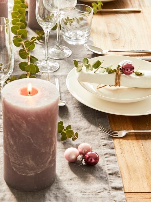 Dekoracja stołu bożonarodzeniowego z różową świecą, bombkami oraz białą zastawą