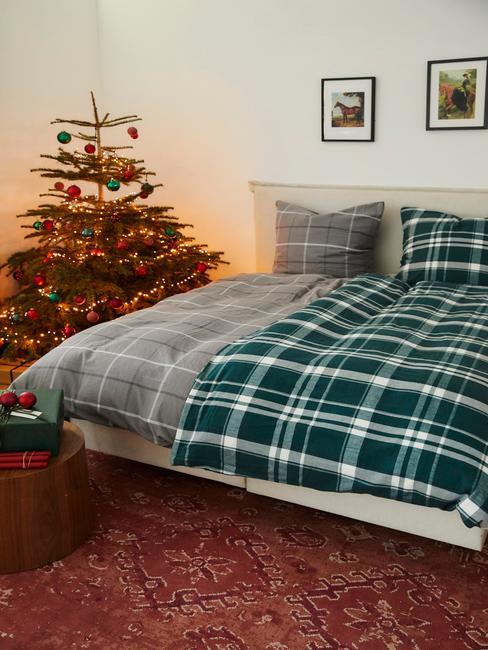 Sypialnia z podwójnym łóżkiem z flanelową pościelom oraz ubraną choinką