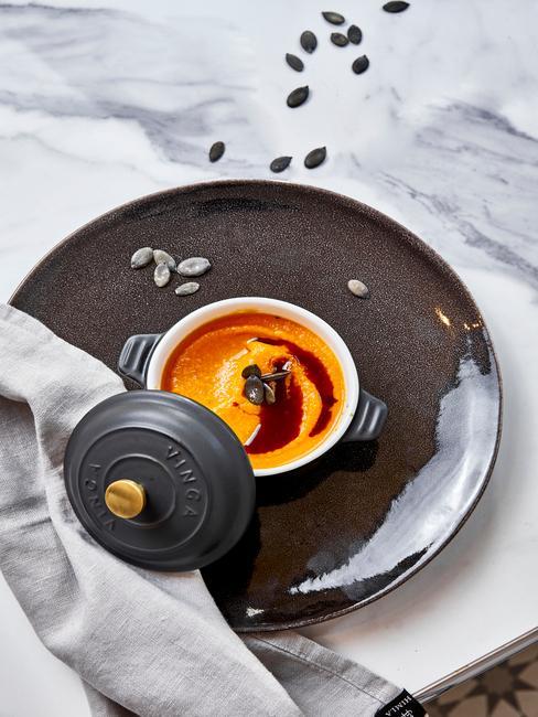 Zupa dyniowa podana w żeliwnym garnku na czarnym talerzu