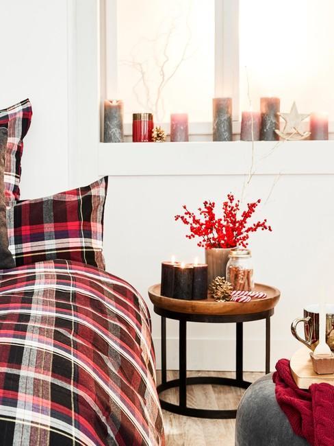 Biała sypialnia z łożkiem z pościlą w kratę, stoliczkiem nocnym praz dużą ilością świec na parapecie