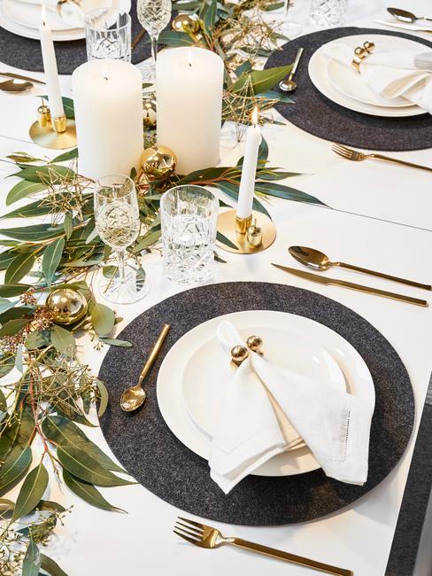 Dekoracja stołu ze stroikiem z liści, złotych sztućców oraz białych świeczek