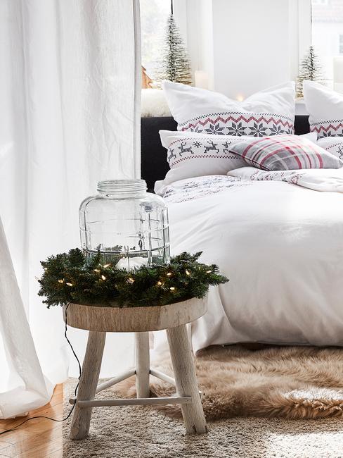 Stroik bożonarodzeniowy ze świecy oraz dużego słoika na stoliku nocnym w sypialni