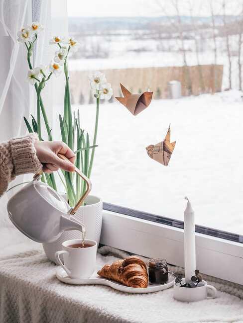 Nálévání čaje u okna.