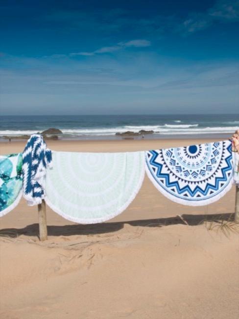 Vue d'une belle plage avec des serviettes à imprimé batik étendues sur un support en bois
