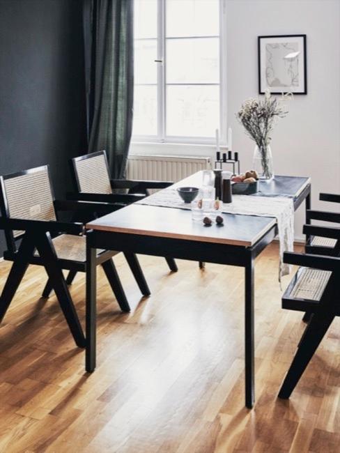 Comedor de estilo casual con mesa y sillas negras con mimbre