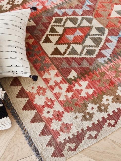 Poduszka z frędzlami na tle kolorowego dywanu