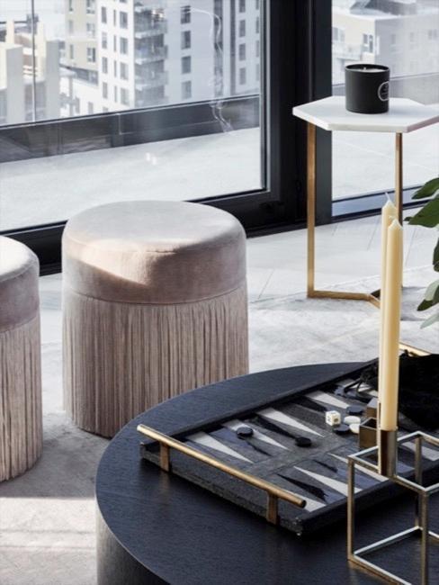 Twee lichte ronde poefs met franjes Adriana met zwarte salontafel op de voorgrond en terracotta fluwelen zitbank op de achtergrond.
