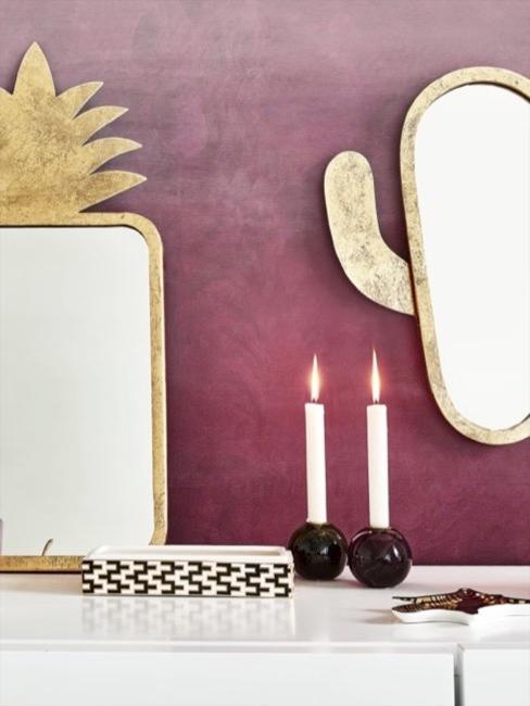 gouden spiegels met kaarsen op witte ladekast voor de rode wand