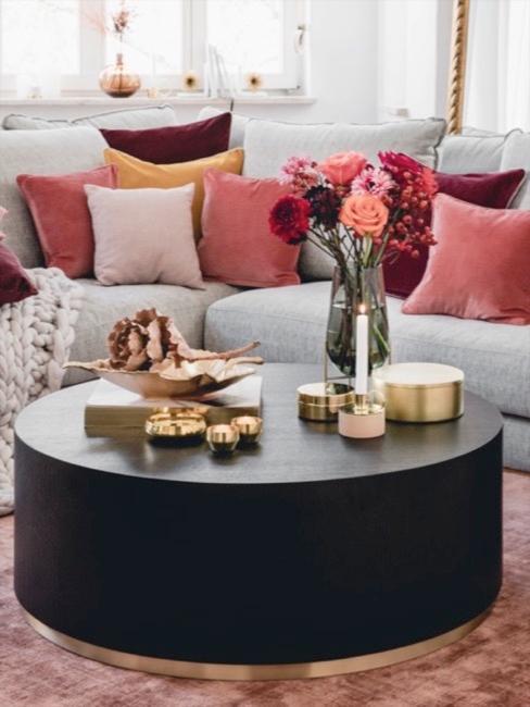 Woonkamer met een grijze bank met rode kussens en een zwarte tafel met gouden decoratie