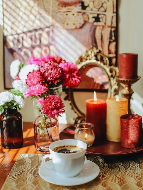 Herbstdeko für den Tisch mit Blumen, Kerzen und Kaffeetasse