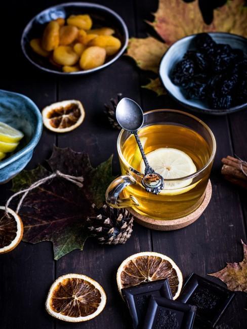 Herbstliche Tischdeko mit Früchten, Zapfen und Schokolade