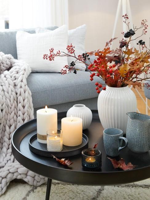Herbstdeko mit Kerzen und Vasen auf dem Beistelltisch